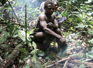 Baka, a Mbendjele pygmy, stops to make a fire in the northern forests of the Congo Republic, while another pygmy behind him holds a GPS handset