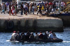 Lampedusa estate 2000. Un gommone carico di immigrati entra in porto sotto gli occhi dei turisti, mentre altri immigrati, arrivati nei giorni precedenti si imbarcano sul traghetto per Porto Empedocle. ©REUTERS/Tony Gentile