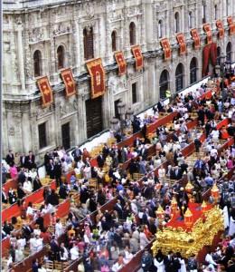 Spettatori paganti variamente occupati mentre per la carrera oficial transita un paso (@ J. A. Zamora, Pasiones. Semana Santa en Sevilla).