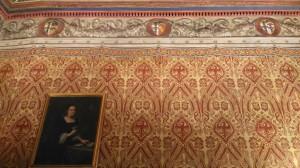 Dettaglio dei broccati del salone. Sono visibili i diversi stemmi che testimoniano le unioni tra la famiglia e altre casate nobiliari (@Niglio 2018).