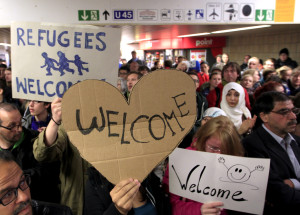 Wellwishers wave to migrants arriving at main railway station in Dortmund