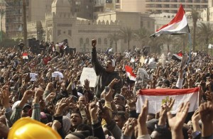 Opposition supporters gesture as they wave the national flags in Tahrir Square in Cairo