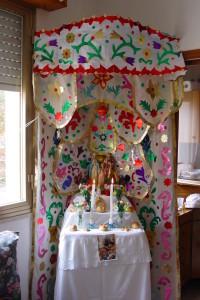 """L' """"Altarino"""" che le famiglie, dell'Isola o emigrate, allestiscono in un angolo della casa.  In una cornice di stole colorate, primeggia una foto della Sacra Famiglia, contornata da  panuzzi,  cucciddati,  arance e vasi colmi di """"barcu"""", simboli obbligati dalla tradizione."""